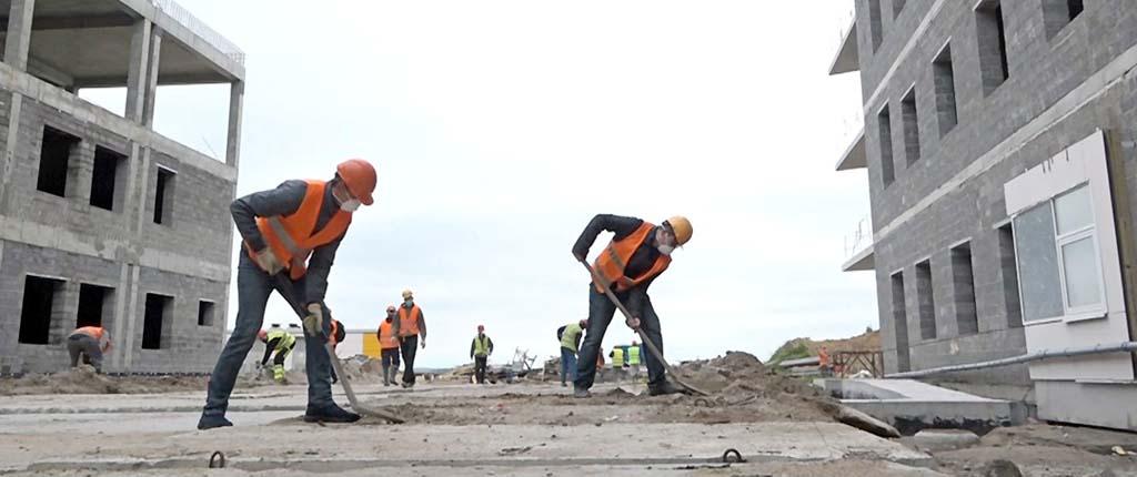 строители машут лопатами